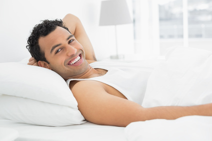 Portrait of a cheerful young man resting in bed at home